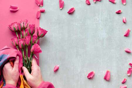 Diagonal geometric paper on stone background. Flat lay, female hands holding pink roses and vibrant trendy scarf, scattered petals around. Top view, greeting for Valentine, birthday or mother's day.