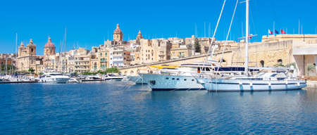 Sailing boats and superyachts on Senglea marina in Grand Bay, Valetta, Malta. Panoramic image of Birgu marina with modern and traditional architecture under blue sky. Stok Fotoğraf