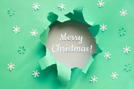 Modern trendy neo mint color paper flat lay with snowflakes and ripped hole with greeting text