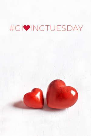 Giving Tuesday, día mundial de donaciones benéficas. Black Friday of Charity, campaña benéfica mundial. Dos corazones de piedra sobre fondo blanco con textura. Brinde ayuda, done, apoye a los necesitados.