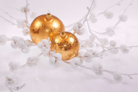 Christmas decorations on light neutral background. Shiny glass golden baubles, trinkets, on neutral white winter background with paper flowers. Wintertime holiday decor with traditional Xmas toys.