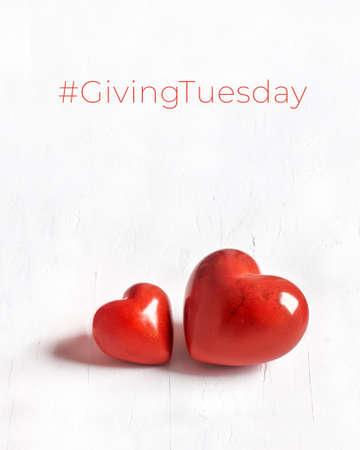 Giving Tuesday, día mundial de donaciones benéficas. Black Friday of Charity, campaña benéfica mundial. Dos corazones de piedra sobre fondo blanco con textura. Brinde ayuda, done, apoye a los necesitados. Foto de archivo