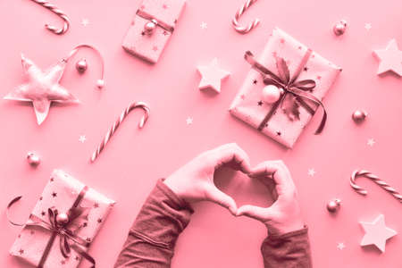 Geometric pink monochrome toned creative flat lay. Two hands forming a heart shape on festive Christmas background with wrapped gift boxes, candy canes, trinkets and stars.