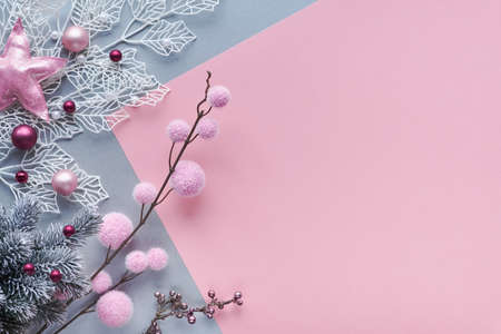 Christmas flat lay in two color paper background, pink and silver, and copy-space. Decorative white winter twigs with shiny geometric leaves, soft textile balls and scattered glass Xmas trinkets.