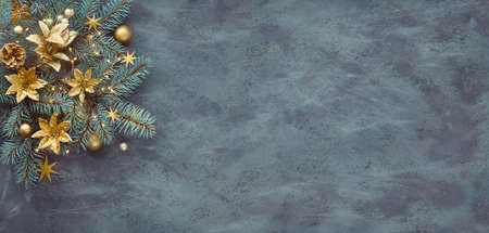 Christmas or New Year panoramic background with fir twigs decorated with golden trinkets, flowers, pine cones and Xmas lights on abstract dark textured background with plenty of text space.