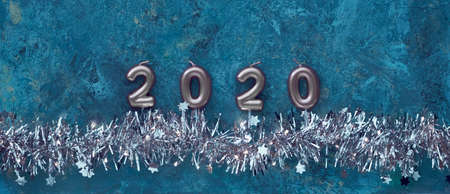 Candle numbers 2020 and shiny sparkling Xmas garland with lights and tiny stars on dark blue grunge textured background, panoramic composition. Merry Christmas and Happy New Year! Imagens