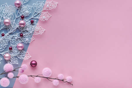 Romantic Christmas flat lay, top view on two color paper background with copy-space. Decorative white winter twigs with frosted geometric leaves and soft textile baubles and scattered glass trinkets.
