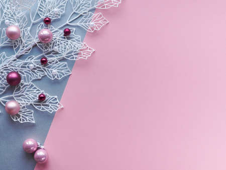 White winter twigs with shiny geometric leaves and scattered glass Xmas trinkets, pink and magenta. Festive Christmas flat lay, top view, two color paper, pink and silver, background with copy-space