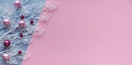 Panoramic Christmas flat lay in two color paper, pink and silver, background with copy-space. White winter twigs with shiny geometric leaves and scattered glass Xmas trinkets, pink and magenta.