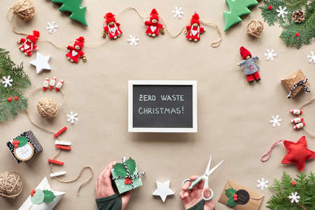 Creative handmade decor, zero waste Christmas frame for new year. Flat lay, top view on craft paper. Textile trinkets, gift box in hand. Eco friendly green Xmas party. Number 2020 on chalk board.