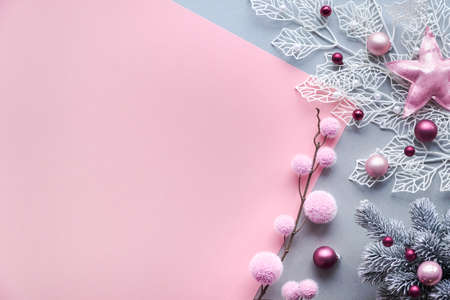 Decorative white winter twigs with frosted geometric leaves and soft textile baubles and scattered glass Xmas balls. Christmas flat lay in two color paper background, pink and silver, copy-space.