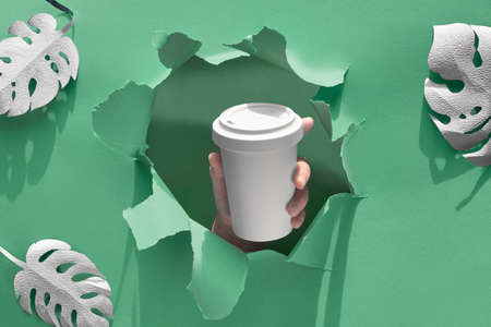 Elegante tazza da viaggio eco caffè riutilizzabile, tazza di bambù con coperchio in mano attraverso il foro della carta. Fondo del libro verde con le foglie esotiche, modello zero spreco del mestiere di carta, spazio della copia. Archivio Fotografico