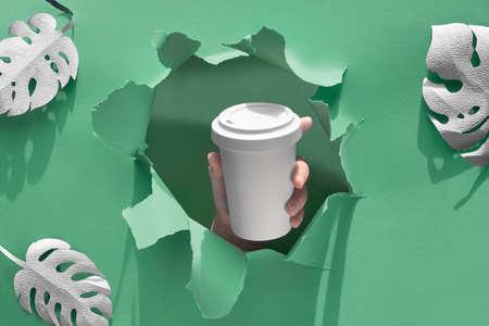 Stilvoller wiederverwendbarer Öko-Kaffee-Reisebecher, Bambusbecher mit Deckel in der Hand durch das Papierloch. Grünbuchhintergrund mit exotischen Blättern, Papierhandwerk null Abfallmodell, Kopienraum. Standard-Bild