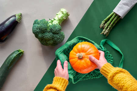 Eco friendly zero waste flat lay with hands holding broccoli and string bag with orange pumpkin. Flat lay with vegetables and cranberry in glass jar on two color background, brown and green paper.