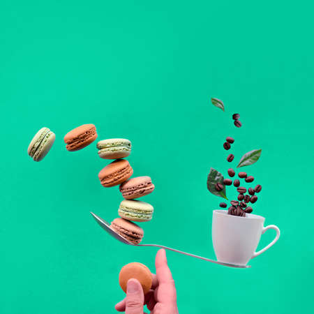 Perfect balance concept. Balancing cup of coffee and macaronos on index finger. Creative square food composition with copy space on trendy Biscay Green paper background.
