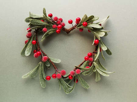 Decorative mistletoe wreath with frosted leaves and red berries shaped as a heart from above. Flat lay, top view on trendy metallic green paper.