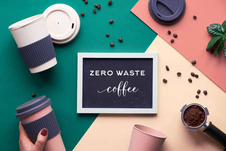 Zero waste coffee concept. Eco friendly reusable coffee cups in hands, geometric flat lay on split paper, creative background in green, beige and yellow with white chalk text on black board. Stock Photo