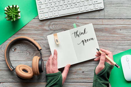 Think green, zero waste creative flat lay. Top view with hands holding notebook with motivation text, wooden workspace with keyboard, computer mouse, succulent plant, earphones on wooden table.