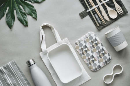 Creative top view, zero waste packed lunch kit, takeaway lunch box set on cotton bag, organizer of bamboo cutlery, bamboo lunch box and reusable cup. Sustainable lifestyle, flat lay on craft paper.