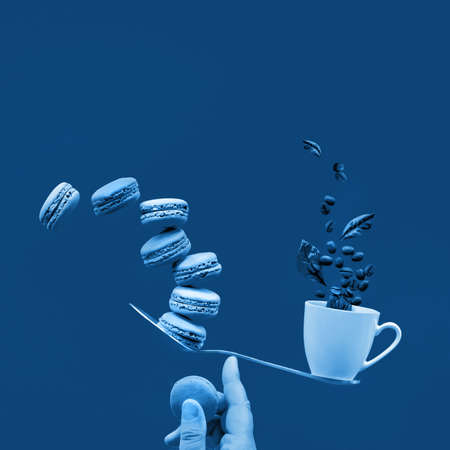 Monochrome blue color toned image. Balancing cup of coffee and macaroons on index finger. Perfect balance concept. Creative square food composition on dark blue square paper background, copy space.