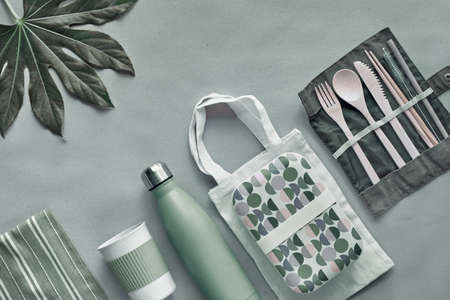 Zero waste packed lunch kit, takeaway lunch box set on cotton bag, organizer of bamboo cutlery, bamboo lunch box and reusable cup. Sustainable lifestyle, flat lay, top view on craft paper.