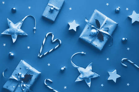 Festive monochrome blue color Christmas background with gift boxes, stripy candy canes, trinkets and decorative stars, geometric creative flat lay with winter decor.