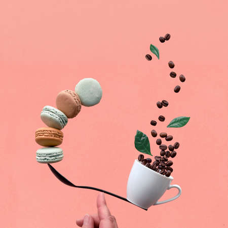 Equilibrium concept flat lay on coral paper background, square composition. Balancing cup of coffee and macarons on a spoon with index finger. Creative coffee background. Foto de archivo