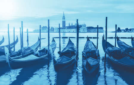 Trendy monochrome image toned in classic blue, color of the year 2020. Gondolas moored by Saint Mark square with San Giorgio di Maggiore church in the background - Venice, Italy.
