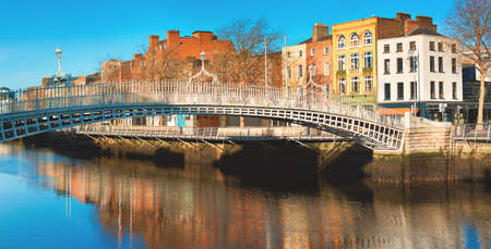 Dublin, panoramic image of Half penny bridge, or Ha'penny bridge, on a bright day with beautiful reflection of historic houses of the riverside in river Liffey Stock Photo