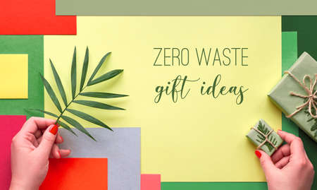 """Multicolor geometric layered paper background, text """"Zero waste gift ideas"""". Creative flat lay, top view of hands holding palm leaf and gift box tied up with cord and decorated with evergreens."""