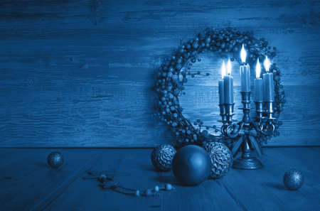 Trendy blue monochrome Xmas composition with candles in candelabrum, berry wreath and classic vintage glass baubles. Vintage Christmas decorations on wood with copy-space.