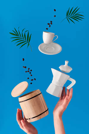 Trendy levitation. Flying line of coffee beans between ceramic coffee maker and espresso cup with saucer. Blue mint background with natural palm leaves.