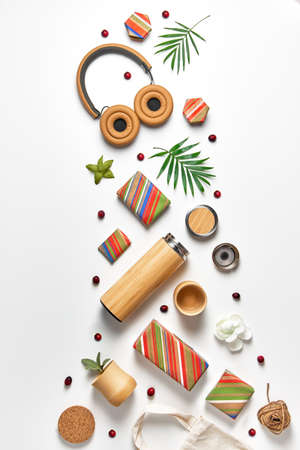 Zero waste wrapped stripy gift boxes, eco friendly gifts, bamboo cups and thermal flask. Geometric creative trendy flat lay, top view on white neutral background with palm leaves and cranberry.