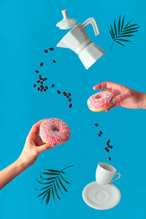 Trendy levitation. Flying line of coffee beans between ceramic coffee maker and espresso cup with saucer. Two female hands hold pink doughnuts with sugar icing. Blue background with palm leaves. 免版税图像