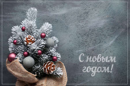 Happy New Year text in Russian language. Small Christmas tree in sackcloth decorated with red trinkets and berries on dark textured background