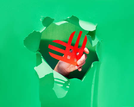 Creative paper lay, top view on the concept of Giving Tuesday or Givingtuesday. Paper craft, long shadows. Paper stripe heart in hand trough a ragged hole torn in trendy neo mint color paper.
