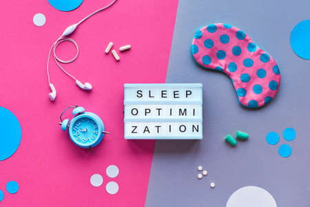 Text Sleep optimization on lightbox. Sleeping mask in polka dots, alarm clock, earphones, earplugs, capsules with sleep remedy. Flat lay, top view, split two tone pink and green paper and circles.