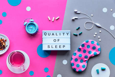 Text Quality of sleep on trendy lightbox. Pink sleeping mask with polka dots, alarm clock, earphones and earplugs. Pills, capsules and calming tea. Flat lay, two tone in pink and silver background.