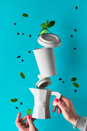 Balancing zero waste coffee pyramid in female hands on blue mint background. Ceramic espresso coffee maker and eco friendly reusable bamboo coffee mug. Coffee beans and leaves fly around..
