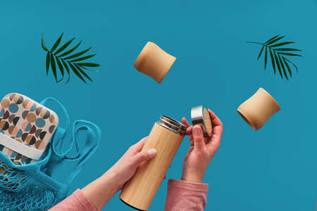 Zero waste tea in in eco friendly insulated bamboo flask. Two hands with cup and palm leaf, net bag with lunch box and tea flask are flying.Zero waste concept levitation on dark tile background. Reklamní fotografie