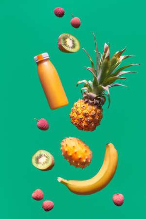 Assortment of tropical fruits and orange smoothie bottle on green background. Pineapple, kiwano, kiwi , lichee and banana - exotic fruits, levitation and balance.