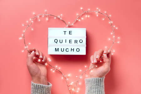 "Valentine flat lay, top view on pink background. Lightbox with text ""Te quiero mucho"" means ""I love you"" in Spanish. Light garland in heart shape held in female hands. St. Valentine's day concept."
