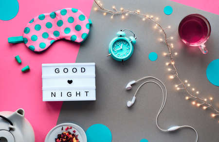 Healthy night sleep creative concept. Sleeping mask, alarm clock, earphones, earplugs, cup of tea and pills. Split two tone pink and craft paper background with light garland. Text Good night.