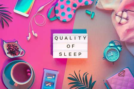Healthy night sleep creative concept. Sleeping mask, alarm clock, earphones, earplugs, tea and pills. Split neon two tone pink green background with palm leaves. Text Quality of sleep on lightbox.