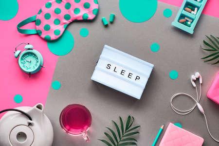 Sleeping mask, turquoise alarm, earphones and earplugs. Calming remedies - pills, capsules and tea. Sleep log notebook. Flat layout, two tone pink and craft paper. Text Sleep on lightbox.