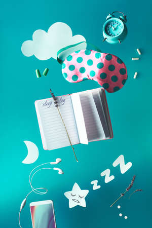 Healthy night sleep creative concept with sleep log handwritten diary. Flying or levitating objects: sleeping mask, alarm clock, earphones, earplugs and pills. Paper moon star and clouds.
