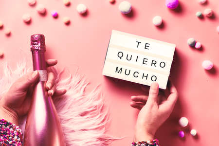 "Valentine day creative flat lay, top view. Hands holding lightbox with text and pink bottle of champagne on abstract pink background. Text ""Te quiero mucho"" means ""I love you"" in Spanish."