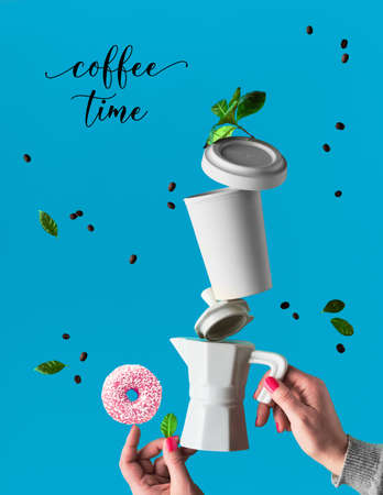 Lévitation à la mode. Ligne volante de grains de café entre la cafetière en céramique et la tasse à expresso avec soucoupe. Des beignets roses avec du sucre saupoudrent l'équilibre sur le doigt. Fond bleu menthe avec des feuilles de palmier.