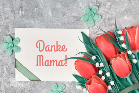 "Danke Mama, German greeting that means ""Thank you Mama"". Greeting on Mother's day on paper card with ribbon. Flat lay - red tulips, green textile flowers and paper card on grey textured background."