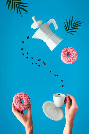 Trendy levitation. Flying line of coffee beans between ceramic coffee maker and espresso cup with saucer. Two female hands hold pink doughnuts with sugar icing. Blue mint background with palm leaves. Banque d'images - 138270221